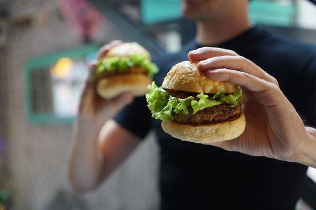 hamburger, muž jej drží v ruce a v druhé taky